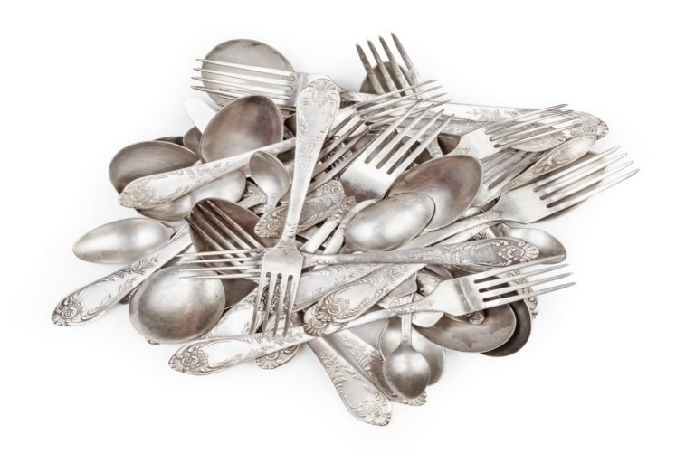 Pile of aged vintage silver cutlery (forks, spoons, knifes) isolated on white background